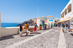 SANTORINI,FIRA-JULY 28: Tourists enjoy view on July 28,2014 in Fira town on the Santorini island, Greece. Royalty Free Stock Photos