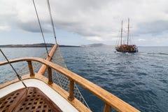 SANTORINI, GRÉCIA - EM MAIO DE 2018: Navios de madeira velhos que navegam no mar Mediterrâneo para o caldera do vulcão fotos de stock