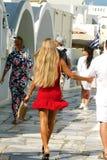 Santorini, Grécia, o 20 de setembro de 2018, menina bonita no vestido vermelho faz a compra nas lojas de Oia fotos de stock