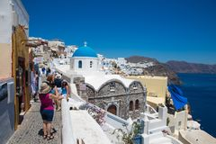 Santorini, Gr?cia: Os turistas dos povos fazem fotos na ab?bada azul do fundo da igreja imagem de stock