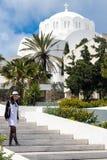 Santorini, Grecia, abril de 2019 Fotografían a una chica joven en un vestido y un sombrero blancos contra la perspectiva de un ch foto de archivo