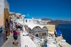 Santorini, Grecia: I turisti della gente fanno le foto sulla cupola blu del fondo della chiesa immagine stock
