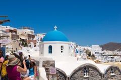 Santorini, Grecia: I turisti della gente fanno le foto sulla cupola blu del fondo della chiesa fotografia stock libera da diritti