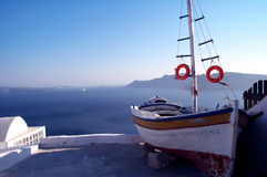 Santorini - Greece. Boat on a terrace by the sea. The sea is blurry due to the haze adding contrast to the boat's sillhouette. Shot in Santorini, Greece stock image