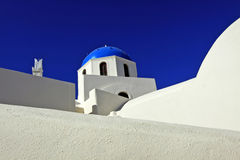 Santorini, Greece. A blue dome and vivid blue sky stand in stark contrast against whitewashed walls in the town of Oia on the island of Santorini, Greece Stock Image