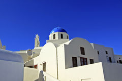 Santorini, Greece. A blue dome and vivid blue sky stand in stark contrast against whitewashed walls in the town of Oia on the island of Santorini, Greece Stock Photography