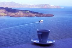 Santorini, Greece, April 2019. Strong delicious coffee in a white cup with a saucer against the backdrop of the sea and a floating royalty free stock images