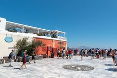 Tourists are visiting central square at Oia town. SANTORINI, GREECE - AUGUST 2018: Tourists are visiting central square at Oia town stock images