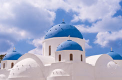 Santorini Greece Church with blue domes and cross against blue sky Stock Photography