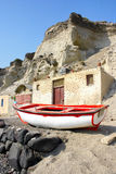 Santorini, Greece: a fisherman boat under the volcanic cliffs Royalty Free Stock Image