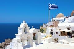 SANTORINI, GREECE - JULY 20, 2018: beautiful view of Oia village with greek flag in Santorini, Greece. stock photo