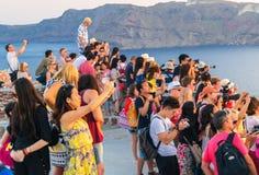 SANTORINI, GREECE - JULY 12, 2014: Tourists enjoy sunset in Oia Stock Photography