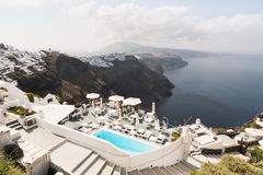 SANTORINI, GREECE - MAY 2018: View over Aegean sea, Firostefani village and volcano caldera with luxury hotel and infinity swimmin. G pool on the foreground stock photo