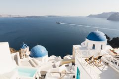 SANTORINI, GREECE - MAY 2018: View over Aegean sea, Oia village and volcano caldera with luxury hotel and infinity swimming pool o. N the foreground. Santorini royalty free stock photo