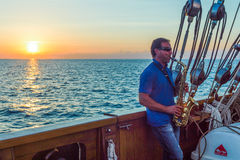 Santorini. Greece - October 13, 2012: A saxophonist plays on a Brigantine in navigation in the Caldera sea area at night fall royalty free stock photo