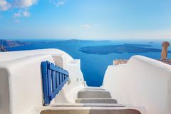 Santorini, Greece. Open blue door with Aegean sea view and Caldera.