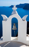 Santorini, Greece. See view and cloudy sky through traditional white church arch and bell in village Oia of Cyclades Island Santorini Greece Royalty Free Stock Photography