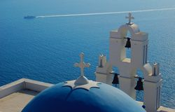 Santorini - Greek Church. Greek church in Santorini, Greece,with view of water and passing boat Royalty Free Stock Photo