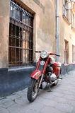 SANTORINI GREKLAND - SEPTEMBER 14, 2013: Röd tappningmotorcykel mot tegelstenväggen Royaltyfri Fotografi