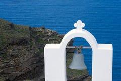 Santorini, Griechenland, im April 2019 Wei?e Haube und Glocke auf einem Hintergrund von blauem Meer, von Insel und von Vulkan stockbild