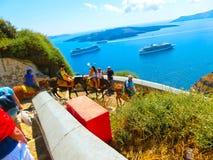 Santorini, Griechenland - 10. Juni 2015: Die Straße zum Meer von den Schritten und vom traditionellen Transport in Form eines Ese Lizenzfreie Stockbilder
