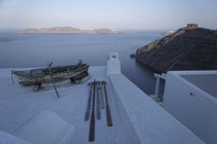 Santorini island. Boat and oars on rooftop of traditional style building on Santorini coastline, Cyclades Islands, Greece Stock Images