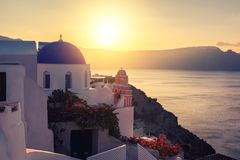 Santorini island in Greece, local church in Oia village on a sun. Sunset over local church with blue cupola in Oia village, Santorini island, Greece. Panoramic Royalty Free Stock Image