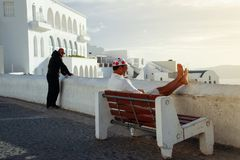 Tourists enjoying the sunset on a bench in the white city of Fira royalty free stock photography