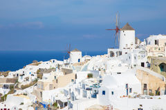 Santorini - kijk aan een deel van Oia met de windmolens Stock Afbeelding