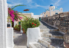 Santorini - kijk mooi met het bloemen decored huis en weinig typisch de wit-blauwe kerk in Oia Stock Afbeelding