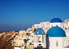 Santorini kopuły błękitni kościół w Oia wiosce, Grecja Zdjęcie Royalty Free
