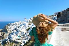 Santorini kvinna som tycker om panoramautsikt av den Oia byn från en terrass, Santorini, Cyclades, Grekland royaltyfri bild