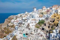 Santorini - la mirada a la parte de Oia con los molinoes de viento y los centros turísticos de lujo Imágenes de archivo libres de regalías