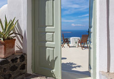 Santorini - little table and easy charis over the caldera. Royalty Free Stock Photography