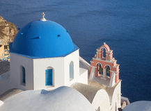 Santorini - The look to typically blue church cupolas with the little bell tower in Oia. Over the caldera Stock Photos