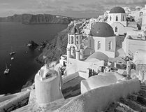 Santorini - The look to typically blue church cupolas in Oia ove. R the caldera and the Therasia island in the background Stock Images