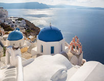 Santorini - look to typically blue church cupolas in Oia over the caldera. Royalty Free Stock Photo