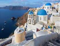Santorini - The look to typically blue church cupolas in Oia. Over the caldera and the Therasia island in the background Royalty Free Stock Photography