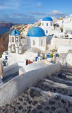 Santorini - The look to typically blue church cupolas in Oia. Over the caldera and the Therasia island in the background Royalty Free Stock Photo