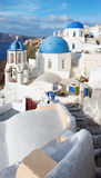 Santorini - The look to typically blue church cupolas in Oia over the caldera. And the Therasia island in the background Stock Image