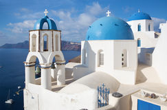 Santorini - The look to typically blue church cupolas in Oia over the caldera and the Therasia island. In the background Stock Photo