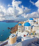 Santorini - The look to typically blue church cupolas in Oia over the caldera. And the Therasia island in the background Royalty Free Stock Photos