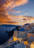 Santorini - The look to typically blue church cupolas in Oia over the caldera and the Therasia island. In the background at sunset dusk Royalty Free Stock Image