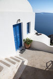 Santorini - look to typically house ower the caldera wiht the white stairs and blue dors in Oia. Stock Photo