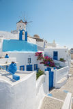 Santorini - mire al molino de viento y a la capilla poco típicamente blanco-azul en Oia Imagenes de archivo