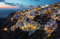 Santorini - o olhar à parte de Oia com os moinhos de vento na luz da noite Fotos de Stock Royalty Free