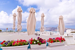 Santorini Oia Outdoor Retaurant, Flowers, Umbrellas, Sky, Clouds Royalty Free Stock Image