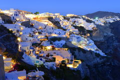 Santorini, Oia village over Aegean sea at sundown. Oia, Santorini, a Greek island with typical white buildings with blue roofs and windows stock photography