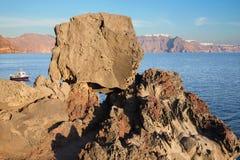 Santorini - olhe ao caldera através dos pedregulhos do polimento com a American National Standard Imerovigili de Scaros no fundo Imagens de Stock