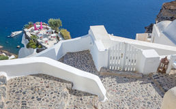 Santorini - The restaurant geared to wedding romantic diner in Oia (Ia) and the yacht under cliffs Stock Images